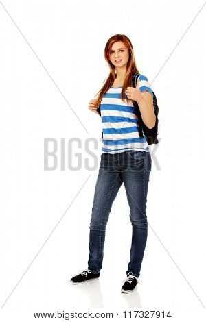 Happy schoolgirl with backpack and thumb up