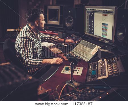 Sound engineer working at mixing panel in the boutique recording studio.