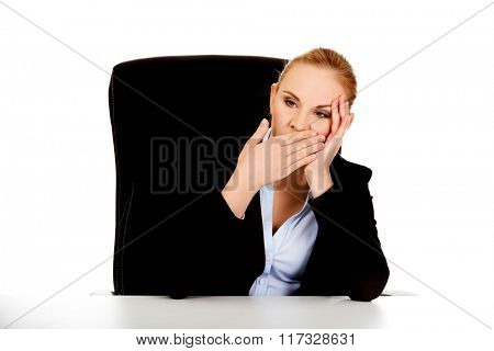 Tired business woman sitting behind the desk and yawning