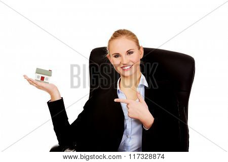Smiling business woman sitting on a chair and holding house model