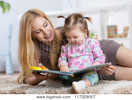 sweet baby girl with mother reading book in nursery