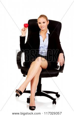 Young business woman holding heart toy