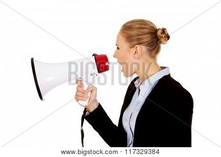 Young business woman screaming through megaphone