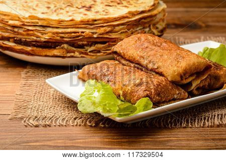 Stuffed pancakes on wooden background.