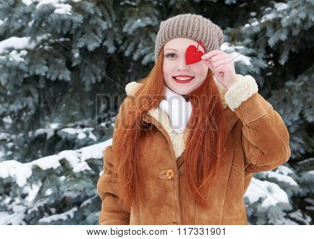 Young woman posing with red heart toy. Winter season. Outdoor portrait in park. Snowy weather. Valentine concept.