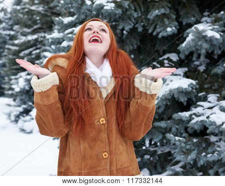 Winter woman joy, looking up on snow, outdoor portrait, snowy fir trees background