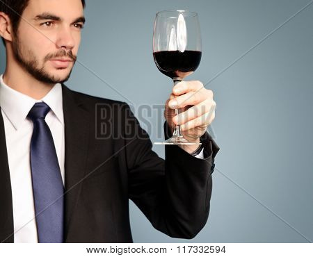 Man looking at the glass of red wine on blue background