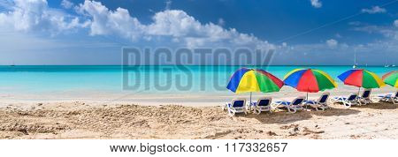 Panorama of chairs and colorful umbrellas on a beautiful tropical beach at Caribbean