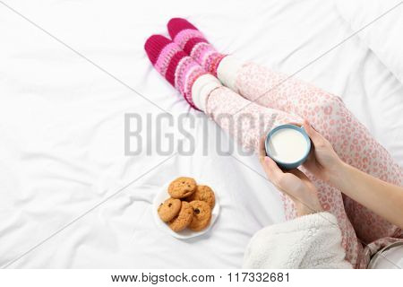 Woman in pajamas holding cup of milk on her bed