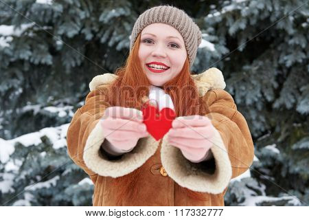 Young woman give red heart toy. Winter season. Outdoor portrait in park. Snowy weather. Valentine concept. Focus on face.