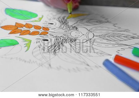 Female hand painting anti stress colouring with felt pen