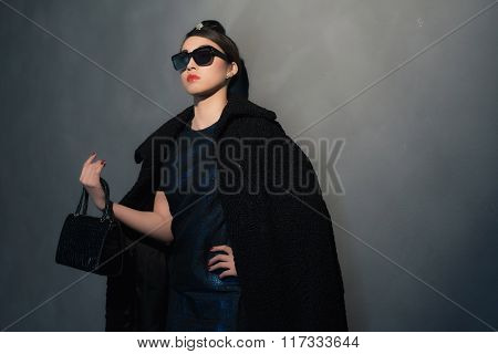 Stylish Wealthy Asian Woman In Retro Forties Fashion With Sunglasses. With Handbag In Her Hand.