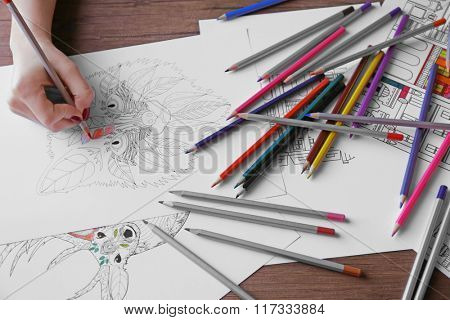 Female hand painting anti stress colouring with red pencil