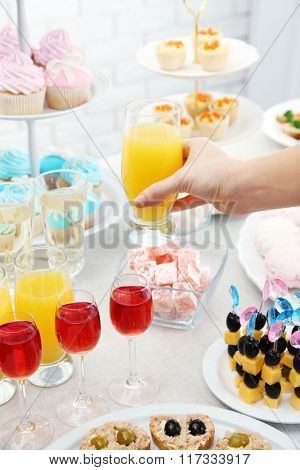 Woman holding glass of juice on buffet background