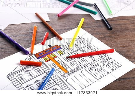 Coloring of buildings with felt pens on wooden table