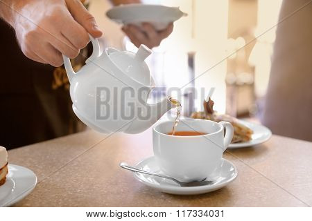 Waiter pouring tea into a white cup in cafe