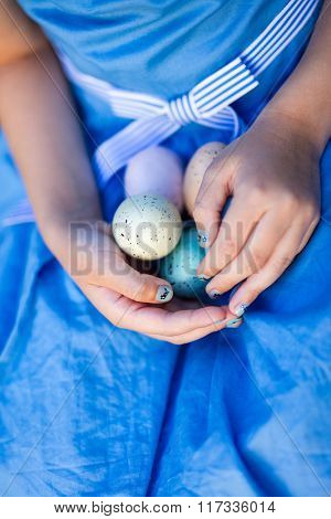 Close up of little girl holding colorful Easter eggs in her hands