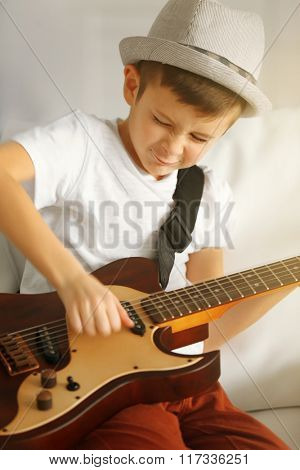 Little boy playing guitar on a sofa at home, close up