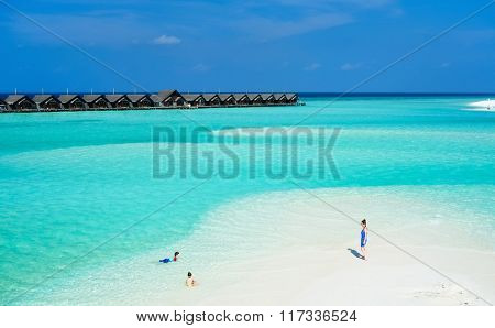 Aerial view of mother and kids enjoying tropical beach vacation