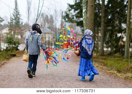 Back view of kids outdoors dressed for Easter traditional celebration in Finland