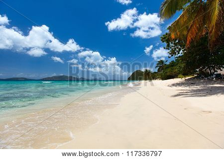 Beautiful tropical beach with palm trees, white sand, turquoise ocean water and blue sky at Tortola, British Virgin Islands in Caribbean