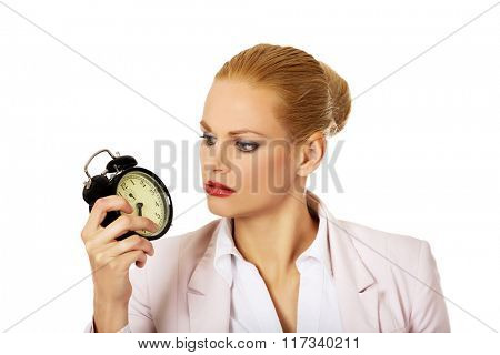 Shocked business woman looking at alarm clock