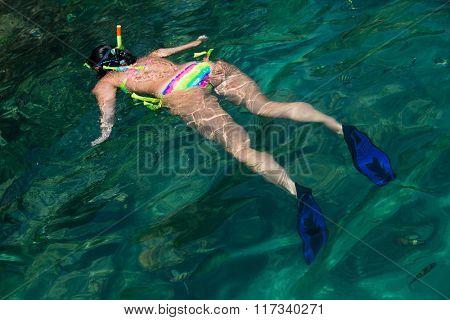 Woman swims among a mask and snorkel. Phi Phi Islands, Andaman Sea, Thailand.