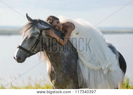 Beautiful  bride, sleeping on a horse in the nature