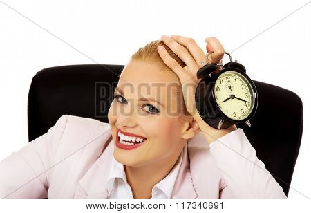 Happy business woman sitting behind the desk and holding alarm clock