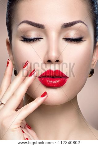 Beautiful Fashion woman model face portrait with red lipstick and red nails. Glamour girl with bright makeup. Beauty female. Perfect skin and make up.