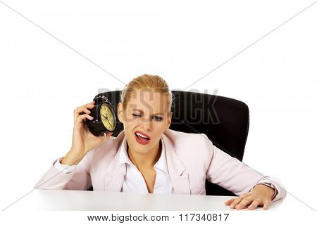 Business woman sitting behind the desk and listen to alarm clock
