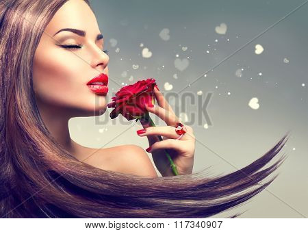 Beauty Fashion Model Woman with red rose flower. Red Lips and Nails. Valentine's Day Beautiful Fashion sexy Girl with flying long hair. Beautiful Sexy Brunette with Luxury Makeup and Manicure