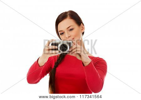 Pretty woman taking a photo using classic slr camera