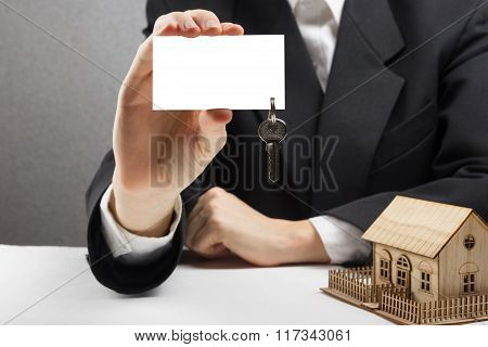 Real estate concept. Agent Hands holding blank business card with keys.