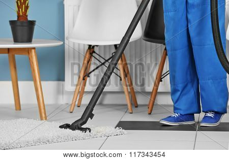 A woman in uniform vacuuming the floor at the office, close-up