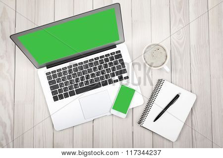 Open notebook, digital tablet and smart phone  on wooden background, top view