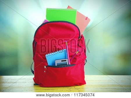 Red bag with school equipment on wooden table in classroom