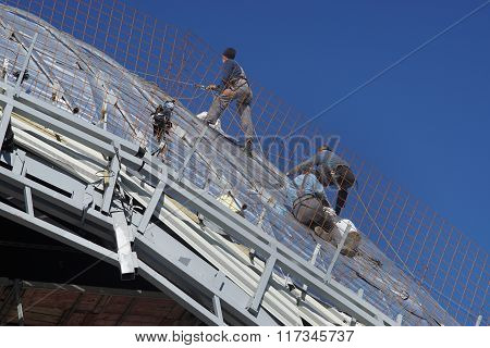 Construction Workers Working On The Roof Of A Building Tied With Ropes
