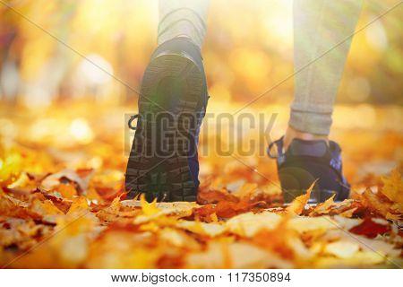 Close-up running feet in autumn park