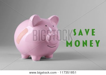 Piggy Bank with adhesive bandage on grey background