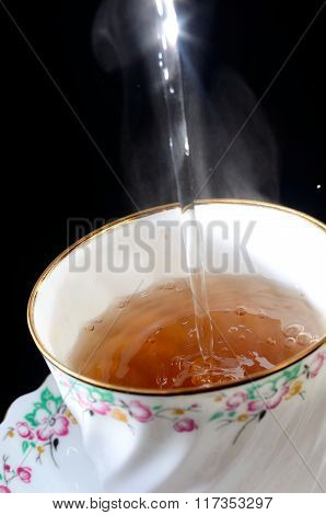 Filling Tea Cup with black tea Isolated On Black