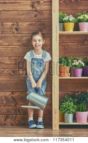Cute child girl caring for her plants. Girl watering flowers in pots. Spring concept, nature and care.