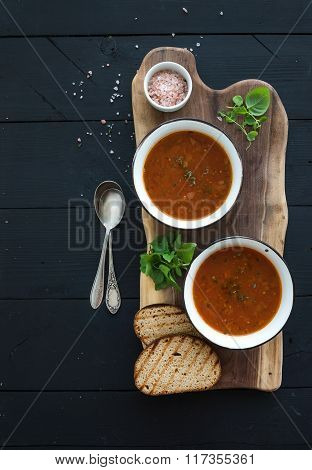 Roasted tomato soup with fresh basil, spices and bread in vintage metal bowl on wooden board over bl