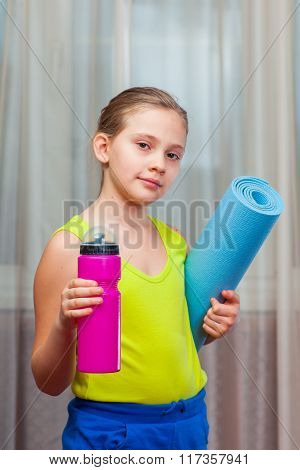 Active Child   holding exercise mat and water bottle in a home