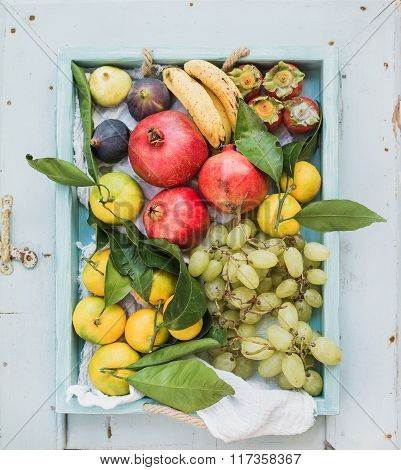 Various colorful tropical fruit selection in blue wooden tray, top view.