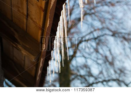 Icicles Hanging On Roof At Winter.