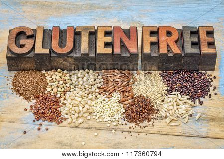 a selection of gluten free grains (quinoa, rice, teff, buckwheat, sorghum,kaniwa, amaranth) and text in vintage letterpress wood type printing blocks against painted wood