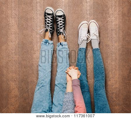 Young fashion couple's legs in jeans and sneakers feet up and holding hands on the wall. Close up. W