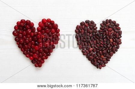 Cranberries And Beans In Heart Shape On Wooden Board