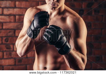 portrait of mma fighter in boxing pose against brick wall